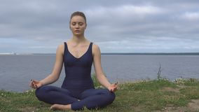 Female in classical yoga pose, energy concentration. Cloudy sky and lake on background. Yogi training, outdoor meditation and healthy lifestyle stock footage
