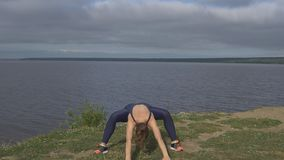 Female in classical yoga pose, energy concentration. Cloudy sky and lake on background. Yogi training, outdoor meditation and healthy lifestyle stock video