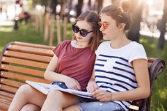 Female classmates sit closely to each other, read information from one book while sit on wooden bench, have focused expressions, d royalty free stock images