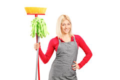 Female cleaner holding a mop and a broom Stock Photography