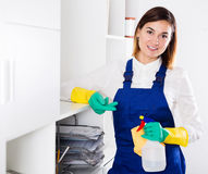 Female cleaner at work. Smiling woman cleaner working effectively on task in office Royalty Free Stock Photography