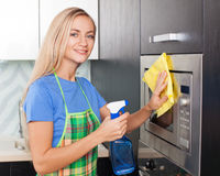 Female cleaning kitchen. Woman cleaning microwave at kitchen. Female doing housework Stock Photo