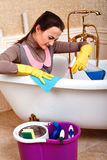 Female cleaning servisce worker sitting in bath Royalty Free Stock Photo