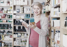Female client browsing rows of skin care products. In specialized shop Royalty Free Stock Photo