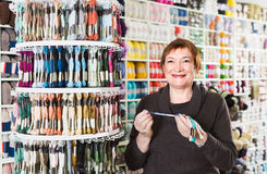 Female client is buying colorful mouline threads. For her hobby Royalty Free Stock Photo