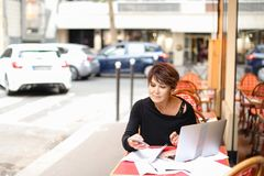 Female client of co-working center make purchases by credit. Female client of co-working working at table with laptop and make purchases by credit card. Aged Royalty Free Stock Photos
