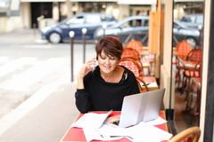 Female client of co-working center make purchases by credit. Female client of co-working working at table with laptop and make purchases by credit card. Aged Royalty Free Stock Photo