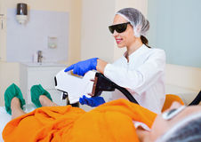 Female client doing laser hair removal from legs. Young  friendly smiling female client doing laser hair removal from legs Stock Photography