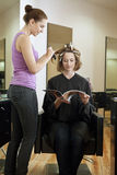 A female client reading a magazine whilst she has her hair coloured in a hairdressing salon stock photo