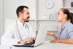 Female client visiting consultation with man doctor Royalty Free Stock Image
