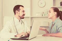 Female client visiting consultation with man doctor Stock Photo