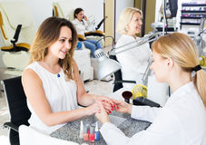 Female clients doing nails in nail salon in afternoon. Happy american female clients doing nails in nail salon in afternoon royalty free stock photography