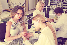 Female clients doing nails in nail salon in afternoon. Smiling american female clients doing nails in nail salon in afternoon stock photo
