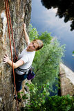 Female Climber. A female climber on a steep rock face looking for the next hold. Shallow depth of field is used to isolate the climber royalty free stock image