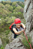 Female climber ascending a rock Royalty Free Stock Photo