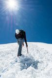 Female climber ascending a snowy slope. Stock Photo