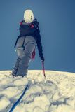 Female climber ascending a snowy slope. Royalty Free Stock Photos
