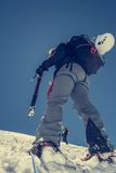 Female climber ascending a snowy slope. Royalty Free Stock Photography
