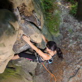 Female climber climbing big boulder in nature with rope. Portrait of strong sporty fit female is climbing the big natural boulder in summer time. Top view Royalty Free Stock Images
