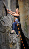 Female climber climbing with rope on a rocky wall. Young beautiful female climber climbing with rope on a steep rocky wall. Summer day Royalty Free Stock Photos