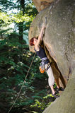 Female climber climbing with rope on a rocky wall Royalty Free Stock Image