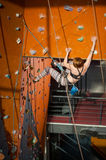 Female climber is climbing up on indoor rock-climbing wall Royalty Free Stock Image