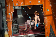 Female climber is climbing up on indoor rock-climbing wall Royalty Free Stock Images