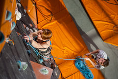Female climber is climbing up on indoor rock-climbing wall Stock Photos