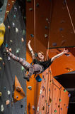 Female climber is climbing up on indoor rock-climbing wall Royalty Free Stock Photo