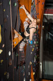 Female climber is climbing up on indoor rock-climbing wall. Young female climber is climbing up on indoor climbing wall and holding one hand in bag with powder Stock Photos