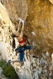 Female climber clinging to a cliff. Stock Photography