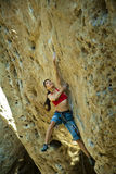 Female climber clinging to a cliff. Stock Photo