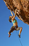 Female climber clinging to a cliff. Female rock climber struggles up a cliff for her next grip on a challenging ascent