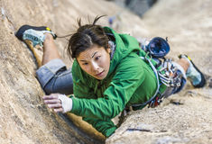 Female climber clinging to a cliff. royalty free stock photos