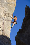 Female climber clinging to a cliff. Stock Image