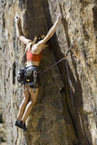 Female climber clinging to a cliff. Royalty Free Stock Images