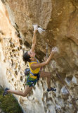 Female climber clinging to a cliff. Royalty Free Stock Photography