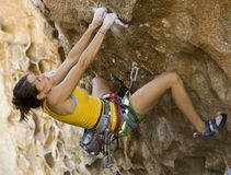 Female climber clinging to a cliff. Royalty Free Stock Image