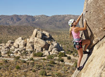 Female climber clinging to the edge. Royalty Free Stock Photo