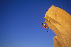 Female climber clinging to the edge. Stock Photos
