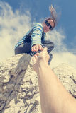 Female climber giving a helping hand. Stock Photography