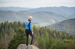 Female climber on the peak of rock with climbing equipment Stock Images
