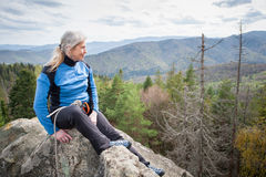 Female climber on the peak of rock with climbing equipment Royalty Free Stock Photo