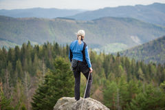 Female climber on the peak of rock with climbing equipment Stock Photography