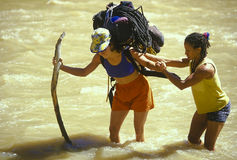 Female climbing team fording river. Stock Image