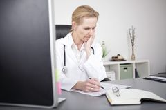 Female Clinician Reading Medical Reports Seriously Royalty Free Stock Photos