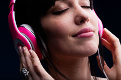Female with closed eyes and grin using headphones Royalty Free Stock Photo
