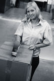 Woman in factory closing box. Factory female closing a box ready to send. Monochrome royalty free stock photo