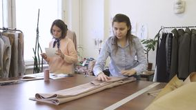 Female clothing designer is laying clothes, standing at table, colleague is making notes, women are working together in. Modern sewing office. In room there is stock video