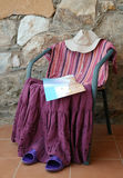 Female Clothing Figure. A figure made of female clothing on the chair with a map in the background of the stone wall Stock Photo